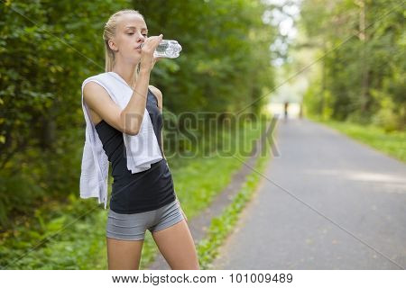 Woman runner drinking water after running