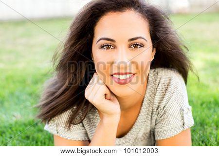 Beautiful ethnic woman sitting outside