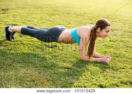 Young woman doing a plank exercise outside