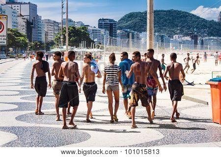 RIO DE JANEIRO, BRAZIL - APRIL 24, 2015: Young spiteful hooligans walking along the boardwalk at Copacabana Beach on April 24, 2015. Rio de Janeiro , Brazil.