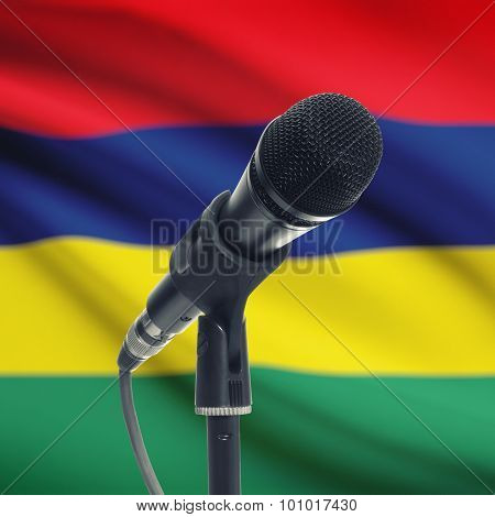 Microphone On Stand With National Flag On Background - Mauritius