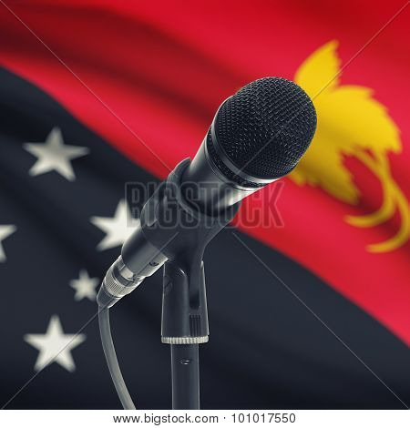 Microphone On Stand With National Flag On Background - Papua New Guinea