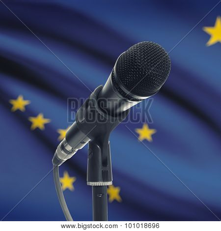Microphone On Stand With Us State Flag On Background - Alaska
