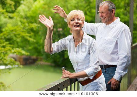 Happy senior couple on bridge waving hands