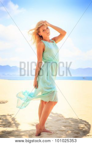 Blonde Girl In Azure Looks Into Distance On Beach