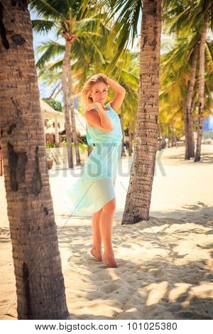 Blonde Girl In Azure On Tiptoe With Hand On Head Among Palms