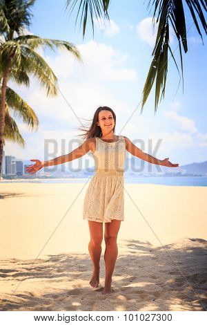 Slim Girl In White Frock Poses With Hands Aside On Beach