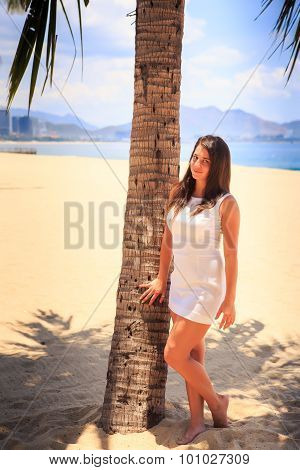 Girl With Big Bust In White Frock Poses By Palm On Beach