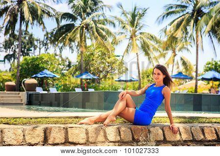 Brunette Girl In Blue Sits On Stone Barrier Against Pool