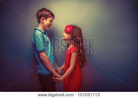 tween girl holding hands teenage boy on gray background retro