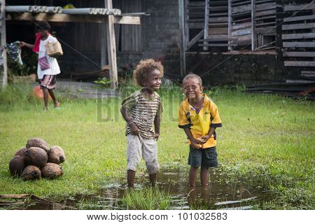 Two kids playing in a puddle