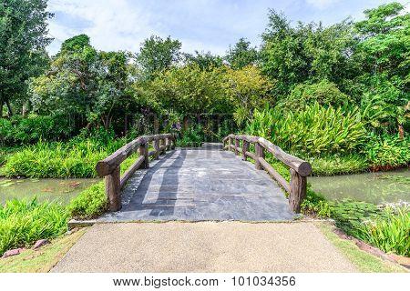 Cement Bridge With Wooden Balustrade Over Pond To Garden.