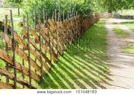 Wicker Fence Or Lath Near Country Road On Sunny Day