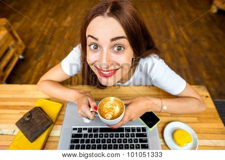 Woman enjoying cappuccino sitting with laptop