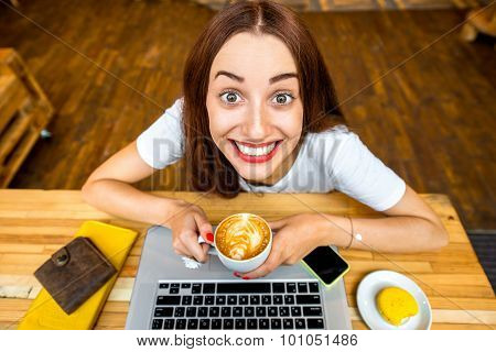 Woman enjoying cappuccino sitting with laptop