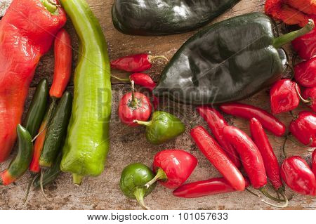 Red And Green Chili Peppers On A Wooden Table