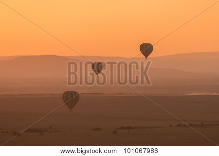 Three Striped Balloons Fly Over Purple Hills