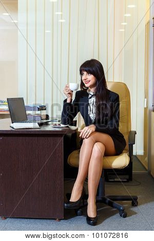 Beautiful Woman In A Short Skirt Drinking Coffee In The Office
