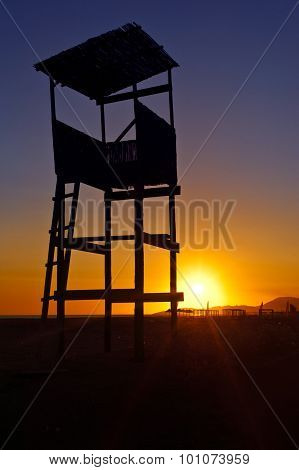 Sunset silhouette of the lifeguard tower