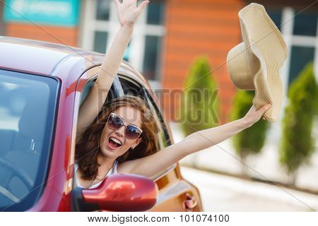 Happy woman driving a red compact car
