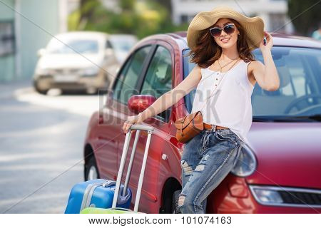 Happy female tourist with suitcases near the car