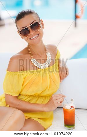 Beautiful woman with a cocktail by the pool on a sun lounger