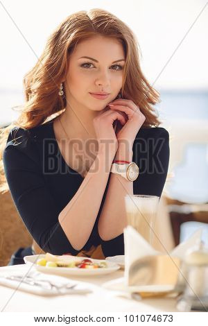 Portrait of a happy woman outdoors in cafe