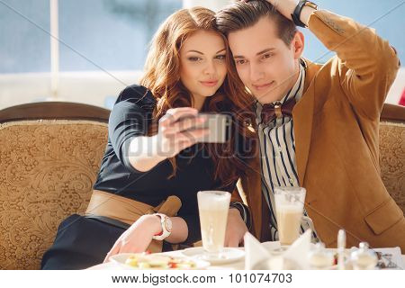 Young couple watching photos on mobile phone, sitting in a cafe