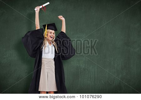 Blonde student in graduate robe holding up her diploma against green chalkboard