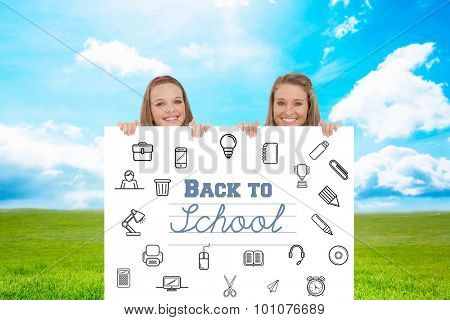 Close up of young women behind a blank sign against blue sky over green field