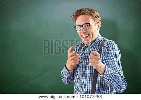 Geeky hipster pointing at camera against green chalkboard