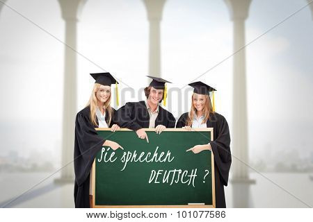 Three students in graduate robe holding and pointing a blank sign against bright room with columns
