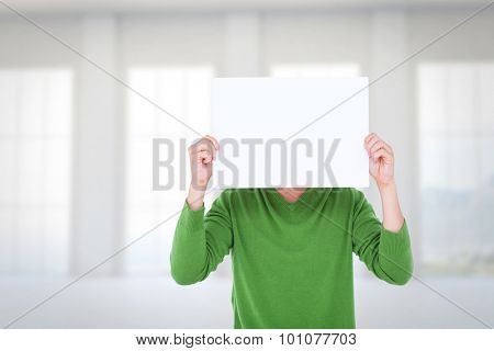 Man holding blank sign in front of face against room overlooking ocean