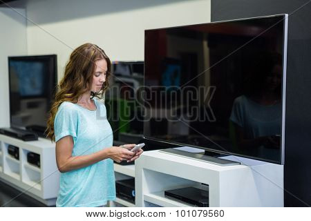 Pretty woman shopping for new television at the electronics store