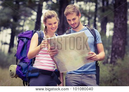 Young happy couple looking at a map in the nature