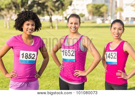 Portrait of three smiling runners supporting breast cancer marathon in parkland