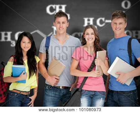 Students looking at the camera as they hold notepads against black background