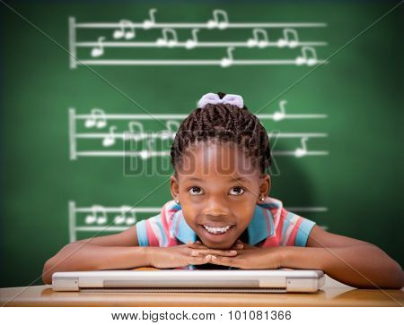 Smiling pupil sitting at her desk against green chalkboard