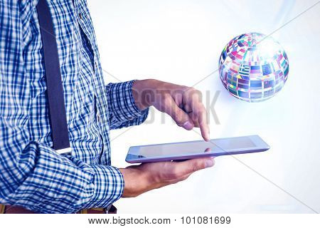 Geeky businessman using his tablet pc against sphere made of flags