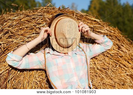 Portrait Of Girl In A Hat On Field With Hay Bales