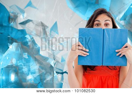 Portrait of a student hiding behind a blue book against angular design