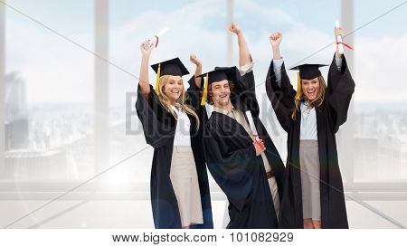 Three students in graduate robe raising their arms against bright white room with windows