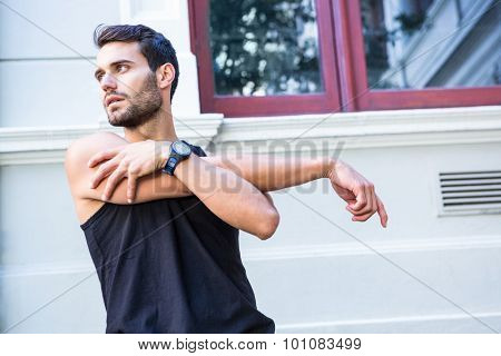 Handsome athlete stretching his arm in the city