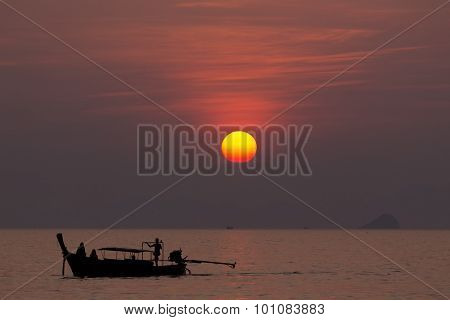 Sunset on tropical sea with traditional Thai fishing boat silhouetted, Thailand