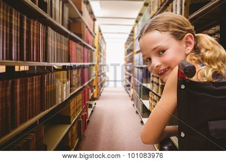 Portrait of cute girl sitting in wheelchair against close up of a bookshelf