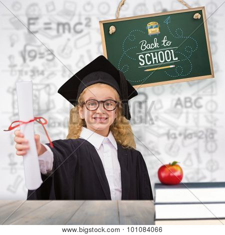 Schoolgirl with graduation robe and holding her diploma against pale grey wooden planks