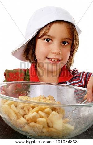 Close-up of an adorable elementary girl smiling over the apple slices she's stirring in with apple pie spices.  On a white background.