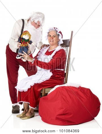 Santa in his work clothes showing his wife the doll he just made while she proudly shows it off for the viewer to see.  On a white background.