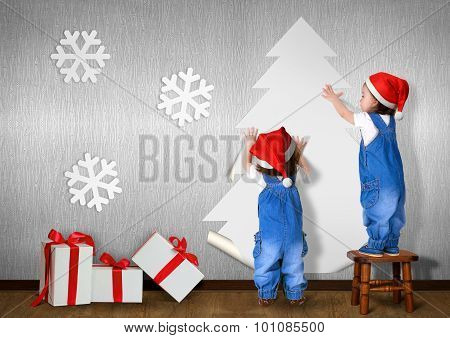 Funny Little Twins Dressed Santa Hat, Glue Christmas Tree On Wall At Home, Xmas Concept