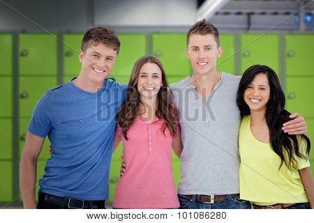 Four friends smiling and embracing each other as they look into the camera against locker room